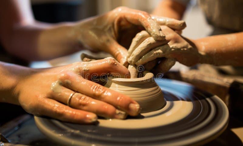 Il vasaio matrice insegna al bambino a lavorare alla ruota del ` s del vasaio Chiuda sul colpo fotografia stock