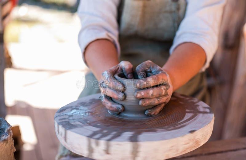 Il vasaio sta creando le terraglie sulla ruota del ` s del vasaio fotografie stock