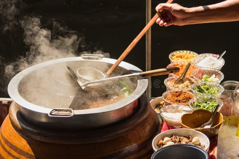 Il vaso è preparato per cucinare Le tagliatelle sono in basso luce, acqua bollente con fumo bianco e vapore su fondo nero fotografia stock