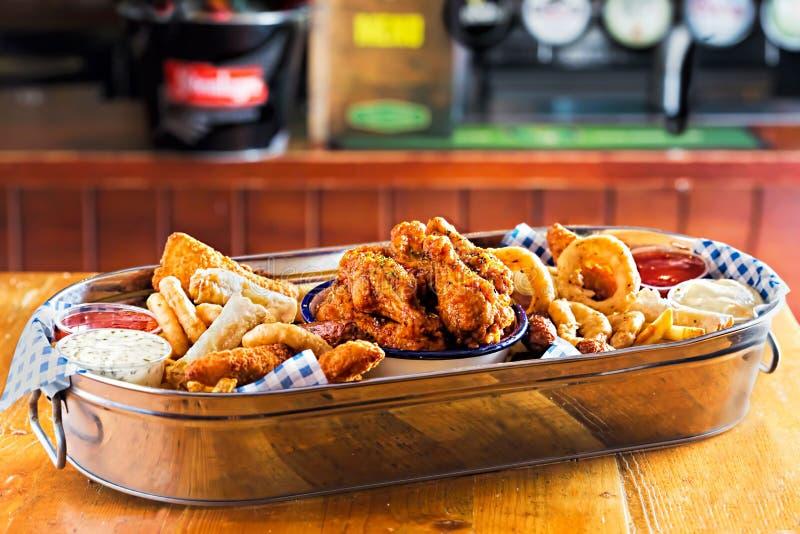 Il vassoio con i goujons del pollo, chook croccante traversa, salsiccie del cocktail, rotoli di molla del veg, anelli di cipolla  immagini stock