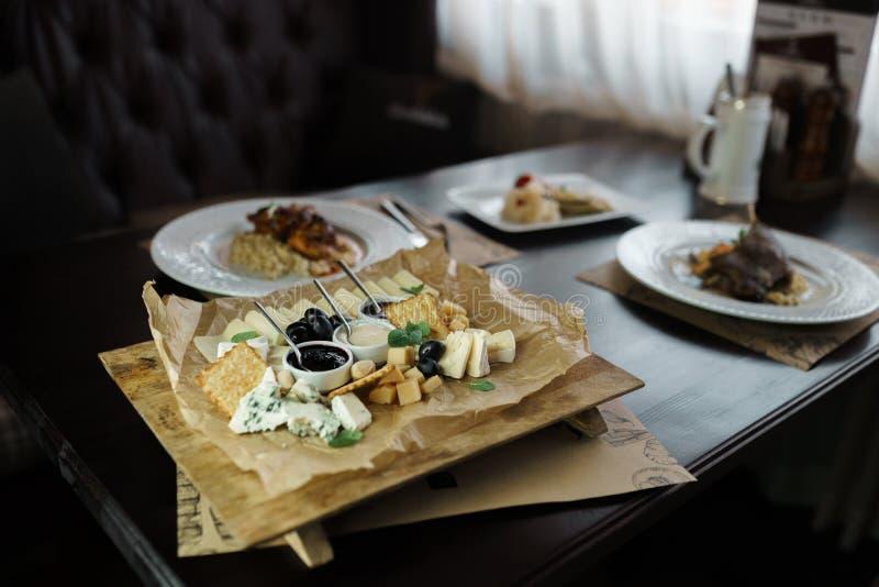 Il vassoio del formaggio su un piatto bianco sta su una tavola d'annata di legno in un ristorante di lusso contro lo sfondo di al fotografia stock libera da diritti