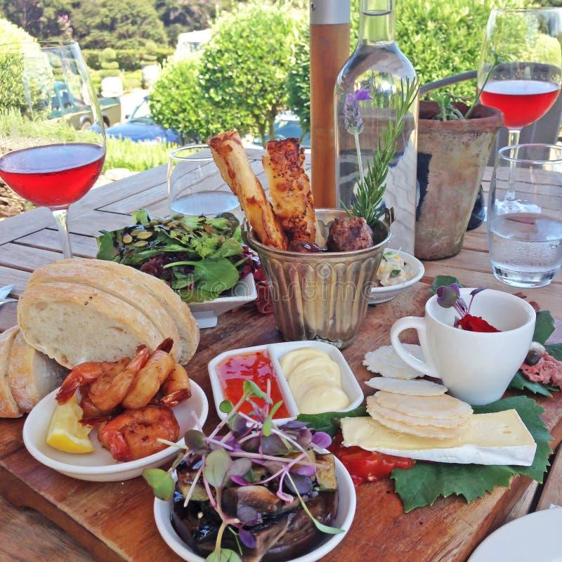 Il vassoio dell'alimento con formaggio, pane, i gamberetti ed il vino rosato è servito fuori fotografia stock libera da diritti