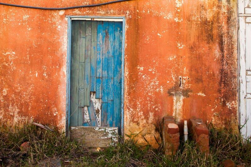 Il vecchio blu ha colorato la porta in casa arancio abbandonata fotografie stock