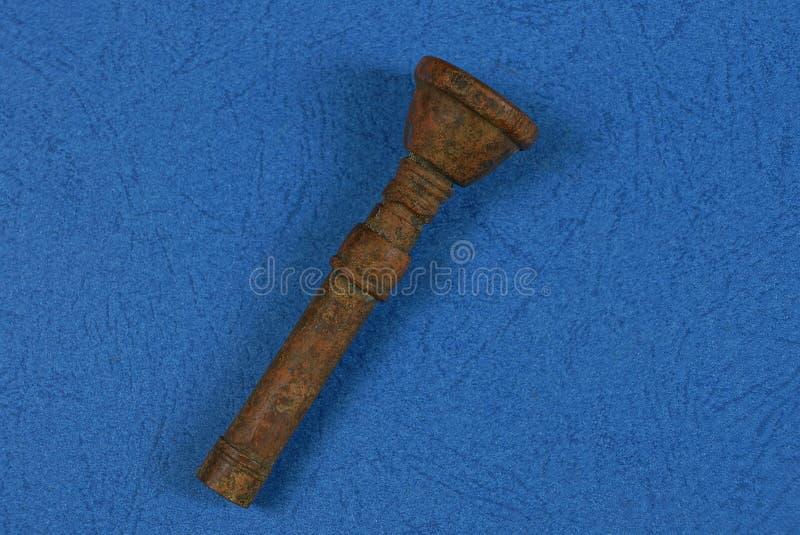 Il vecchio boccaglio bronzeo si trova su una tavola blu fotografie stock libere da diritti