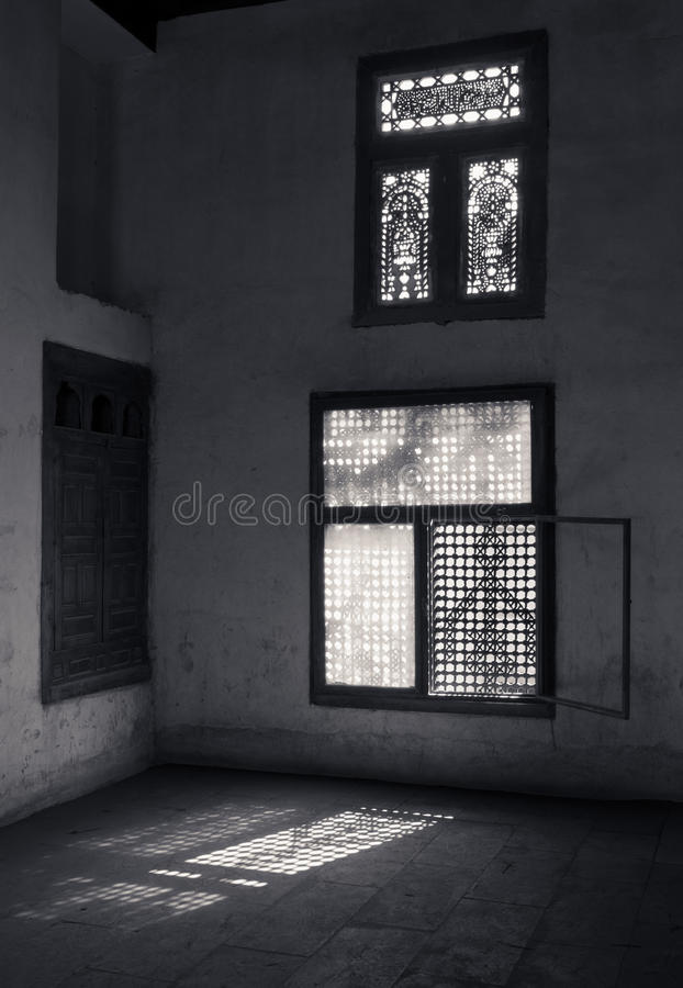 Il vecchio buio abbandonato ha danneggiato la stanza sporca con due finestre decorate rotte di legno immagini stock