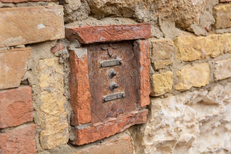 Il vecchio campanello per porte rustico in pietra ed in mattone ha fatto la facciata immagini stock