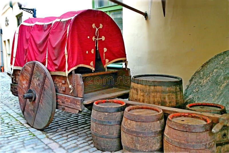 Il vecchio carretto accanto ai barilotti di birra vuoti Una via stretta di vecchia città immagine stock