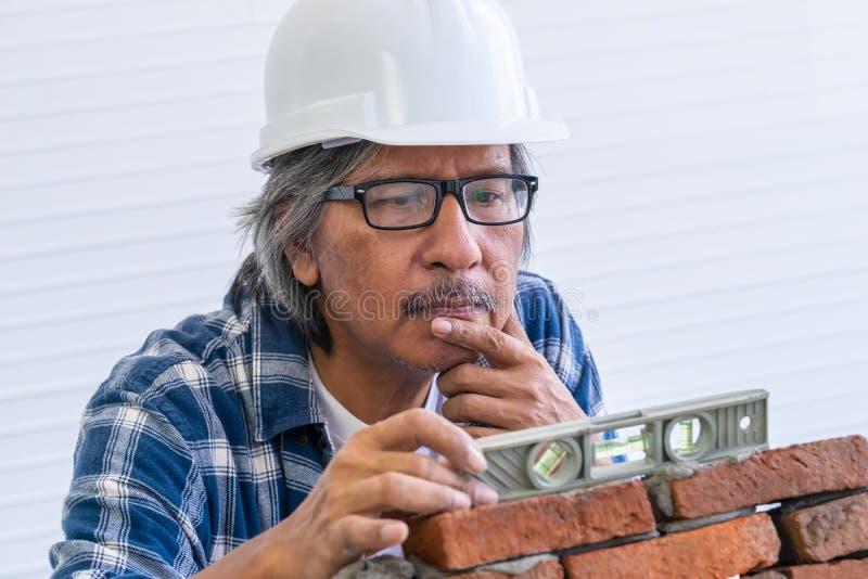 Il vecchio costruttore sta livellando il muro di mattoni immagini stock libere da diritti