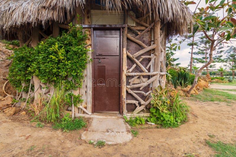 Il vecchio cottage fatto dei tronchi di albero con la porta marrone di legno chiusa di lerciume e ricopre di paglia il tetto, cir fotografia stock libera da diritti