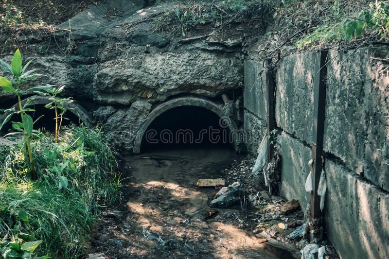 Il vecchio drenaggio concreto convoglia con il tubo scorrente dell'acqua di scarico, delle acque luride o del tunnel della fognat immagini stock