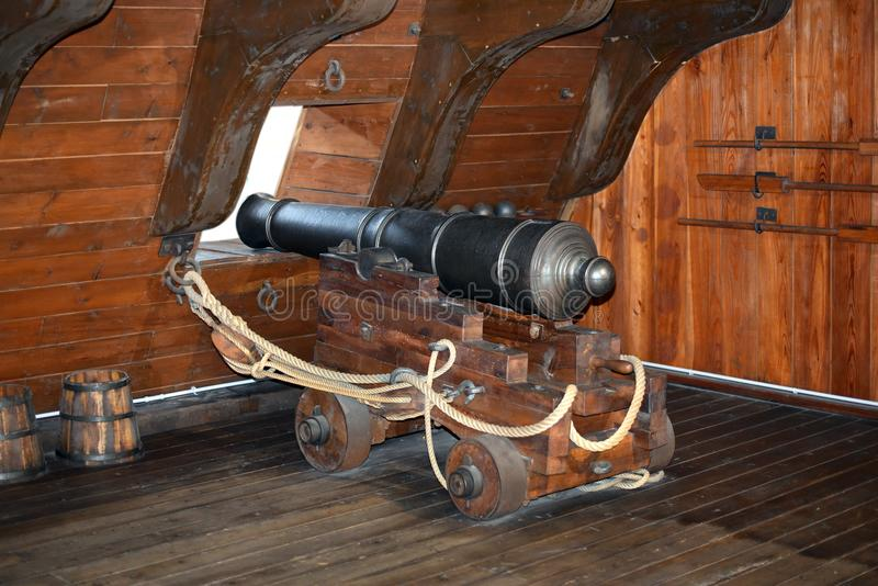 Il vecchio ferro spedisce il canone posizionato ad un oblò immagini stock