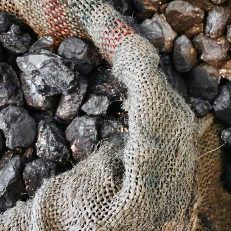 Il vecchio fuori sacco consumato della iuta, riempito di pezzi di cavolo, carbone ha offuscato intenzionalmente, energia fotografia stock libera da diritti