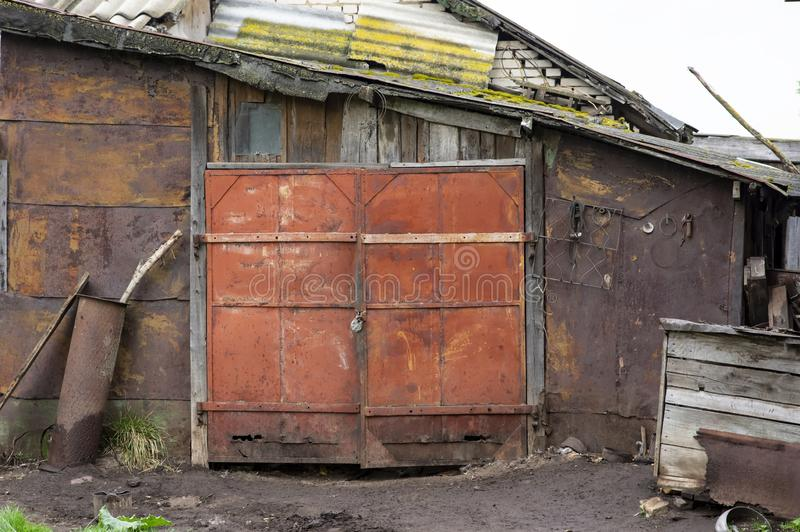 Il vecchio garage, ha sparso con i portoni arrugginiti immagine stock