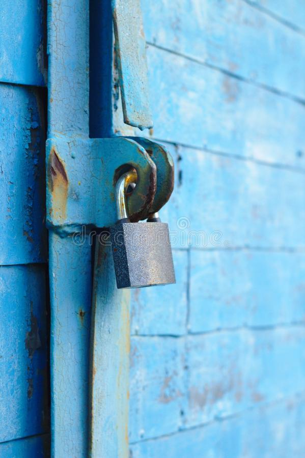 il vecchio lucchetto su una porta blu del metallo con le plance di legno ha fenduto la pittura e la ruggine immagini stock