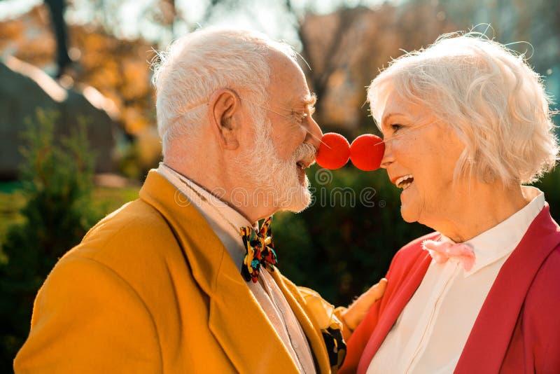 Il vecchio marito e la moglie sorridenti con il naso da clown nel parco immagini stock