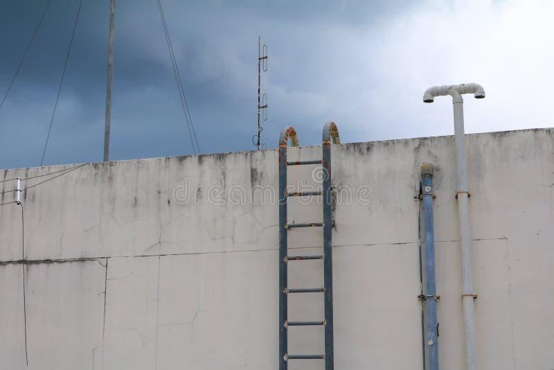 Il vecchio metallo industriale verticale della scala ha arrugginito al serbatoio di acqua nessun battagliole immagini stock