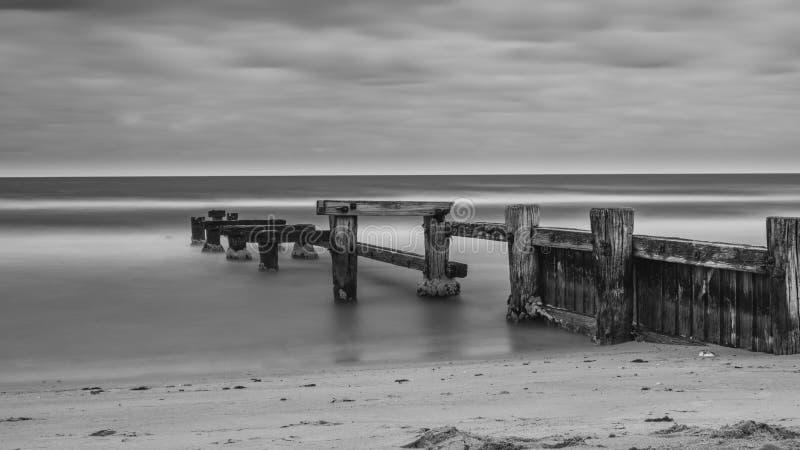 Il vecchio molo della spiaggia di Mentone in bianco e nero immagine stock libera da diritti