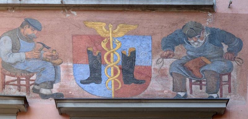 Il vecchio murale sulla facciata della casa mostra un calzolaio medievale sul lavoro nel centro urbano di Zurigo fotografia stock