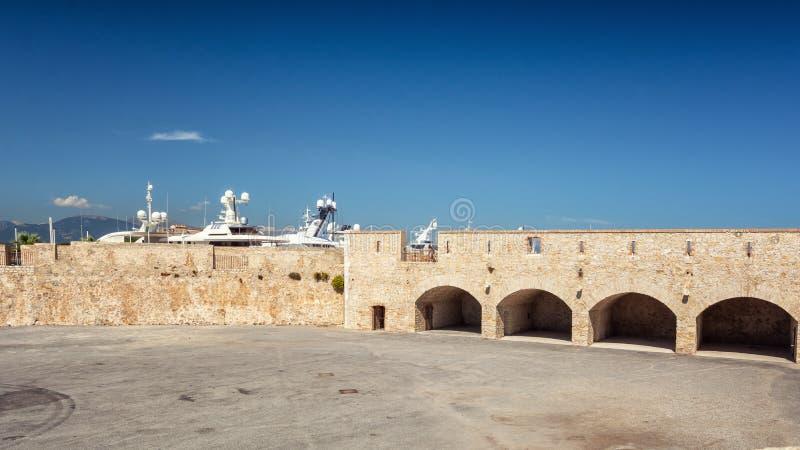 Il vecchio muro di cinta di porto Vauban a Antibes con nei precedenti gli yacht eccellenti messi in bacino immagine stock