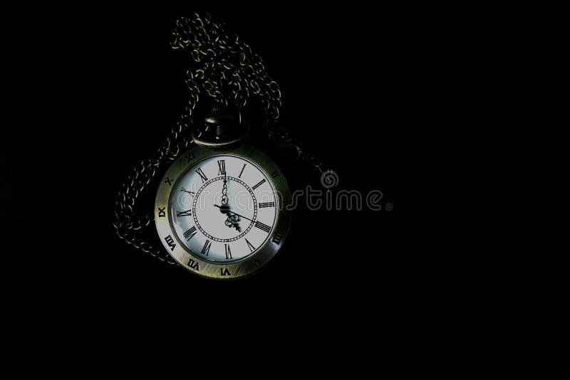 Il vecchio orologio da tasca ? una collana che ? separata su un fondo nero fotografia stock libera da diritti