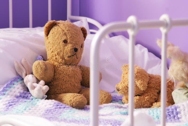 Il vecchio orsacchiotto trasandato riguarda la base del bambino fotografia stock