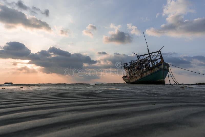 Il vecchio peschereccio rovinato di legno stabilito in secca sulla spiaggia a tempo di tramonto immagini stock