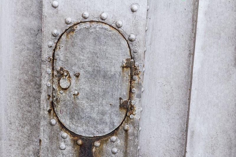 Il vecchio piatto del metallo ha sopravvissuto la parte ovale della porta grigia dei ribattini della base industriale di progetta immagine stock