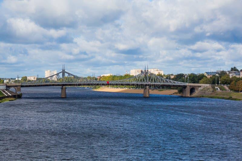 Il vecchio ponte di Volga sopra il fiume e la spiaggia nella città di Tver', Russia Nuvole pittoresche nel cielo fotografia stock libera da diritti