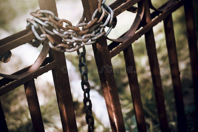 Il vecchio portone abbandonato è chiuso da una catena arrugginita immagini stock libere da diritti