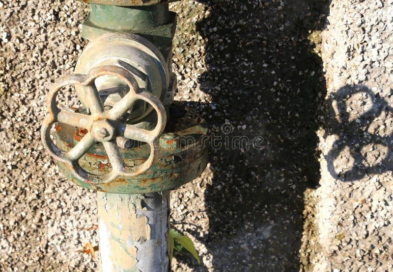 il vecchio rubinetto arrugginito e l'acqua annaffiano nel giardino fotografie stock libere da diritti