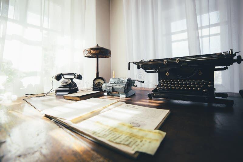 Il vecchio scrittorio con una macchina da scrivere e l'annata telefonano fotografie stock