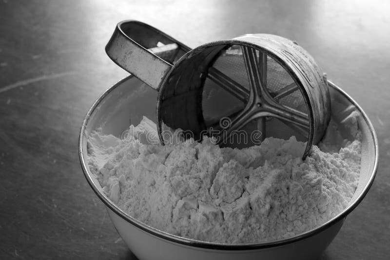 Il vecchio setaccio della farina della tazza dell'acciaio inossidabile si trova in una ciotola bianca dello smalto con la farina  fotografie stock