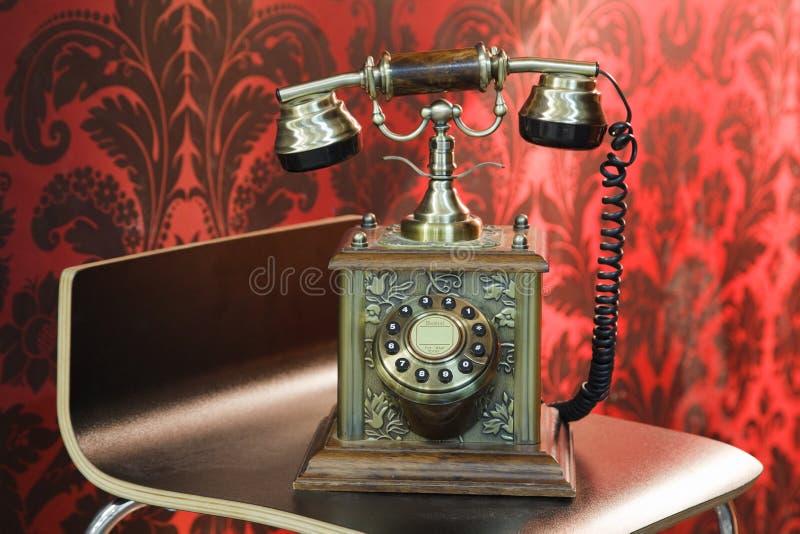 Il vecchio telefono si leva in piedi sulla presidenza di legno immagini stock