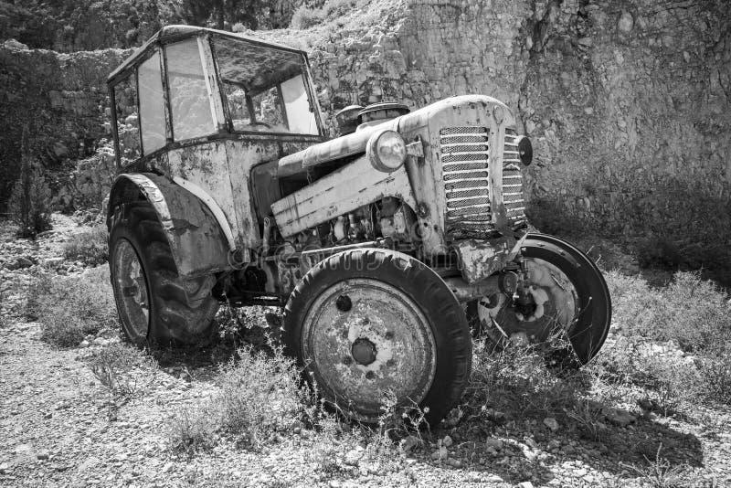 Il vecchio trattore arrugginito abbandonato sta su erba immagine stock