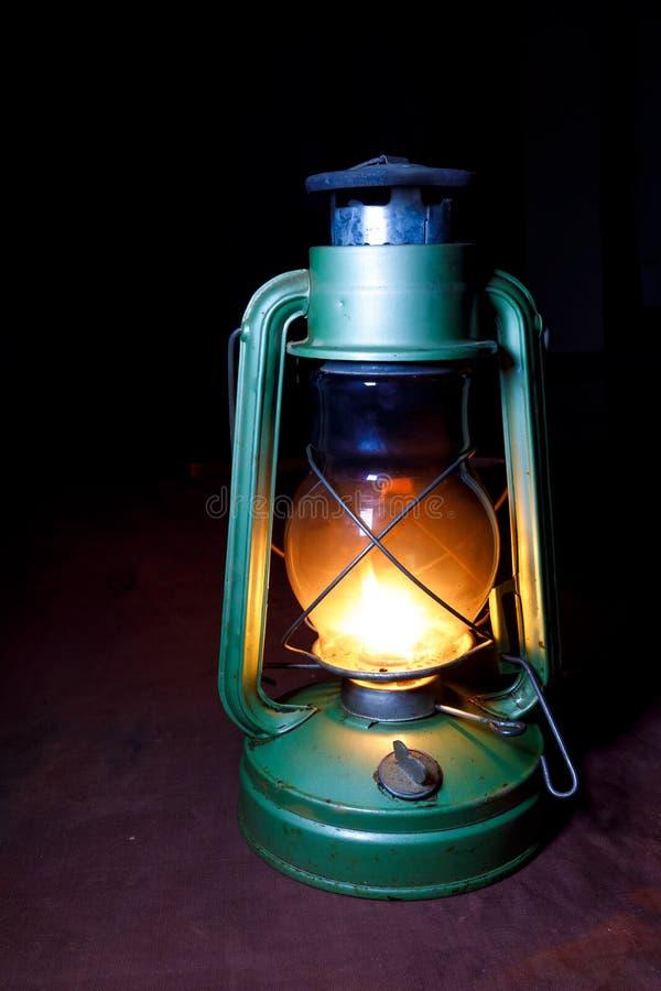 Il vecchio verde indossato della lampada di cherosene è nel cuore della notte sul fondo di Borgogna immagine stock libera da diritti