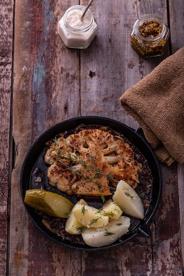 Il vegetariano ha arrostito la bistecca del cavolfiore con le patate su una padella fotografia stock libera da diritti