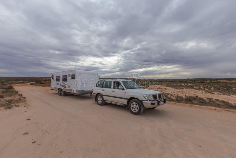 Il veicolo di quattro ruote motrici ed il grande caravan hanno parcheggiato sulla pista di un'entroterra fotografie stock