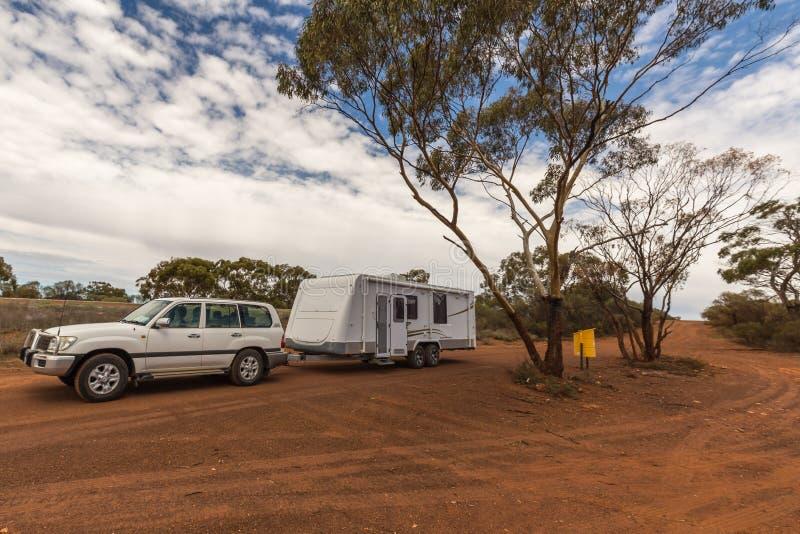 Il veicolo di quattro ruote motrici ed il grande caravan parcheggiati in un resto si fermano fotografia stock libera da diritti