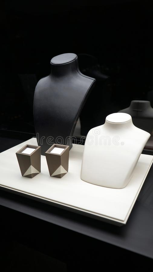 Il velluto vuoto dei gioielli corrisponde alle collane ed a due scatole su un vassoio Interno in bianco e nero del boutique immagini stock libere da diritti