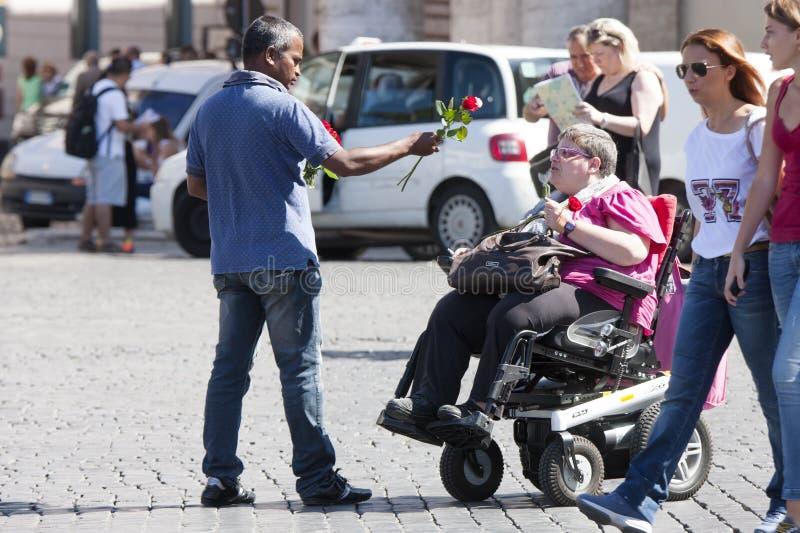 Il venditore ambulante delle rose prova a vendere una signora disabile fotografia stock