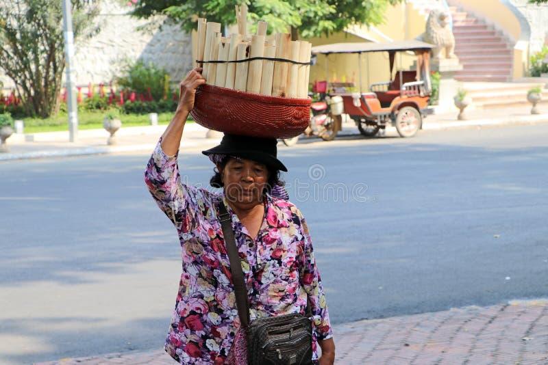 Il venditore ambulante femminile cambogiano ha messo il canestro di riso appiccicoso inzuppato in latte di cocco e cotto in una s immagine stock