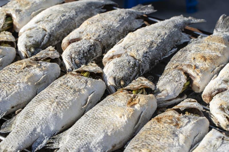 Il venditore ambulante tailandese vende il pesce arrostito al mercato di strada in Koh Phangan, Tailandia Fine in su fotografia stock libera da diritti