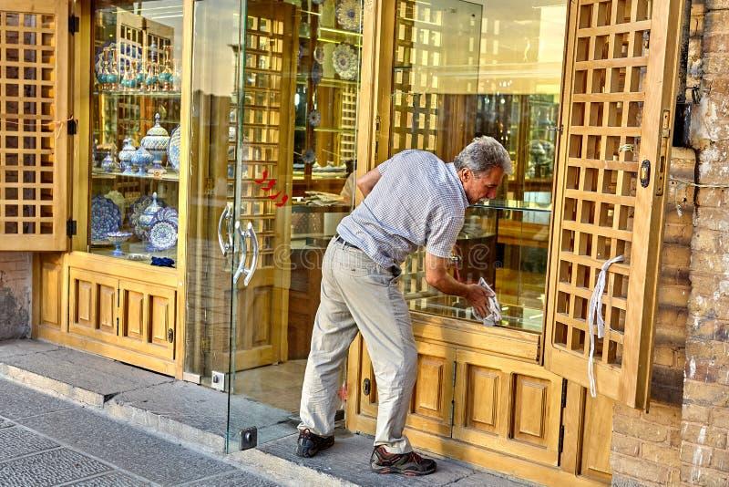 Il venditore di porcellana lava la finestra del negozio, Ispahan, Iran fotografia stock