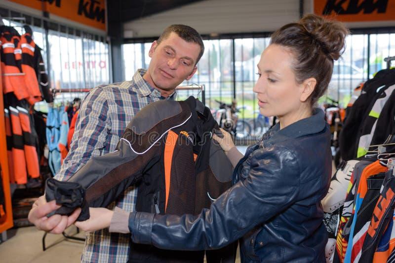 Il venditore grazioso mostra il cappotto della motocicletta al cliente al deposito immagini stock libere da diritti