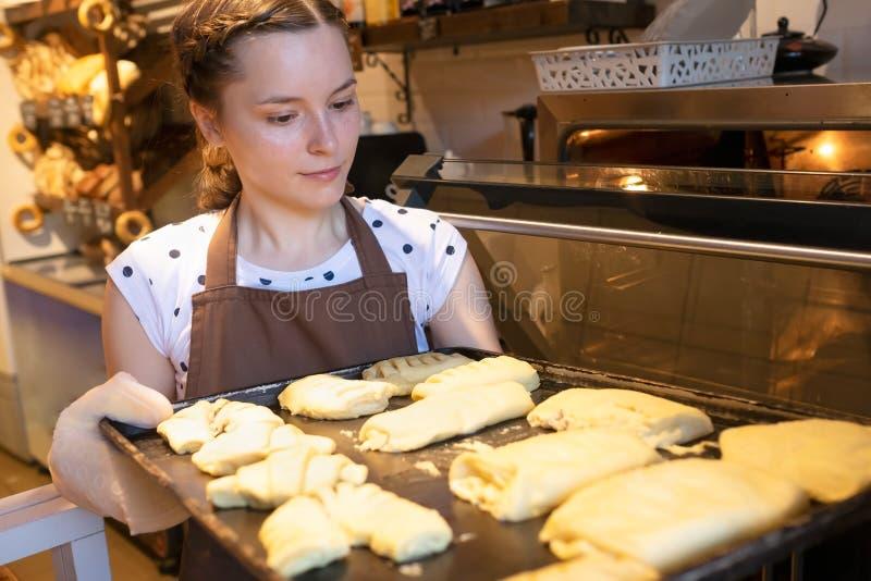 Il venditore mette il vassoio bollente in forno che cucina le torte fresche immagini stock libere da diritti