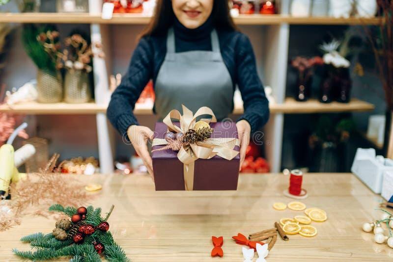 Il venditore mostra il contenitore di regalo con lo spostamento fatto a mano fotografia stock