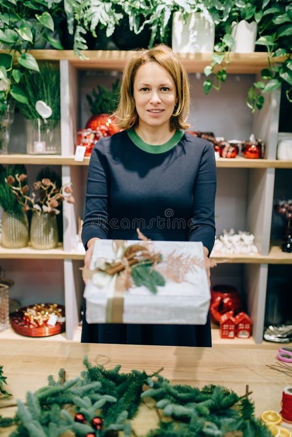 Il venditore mostra il contenitore di regalo con lo spostamento fatto a mano fotografia stock libera da diritti