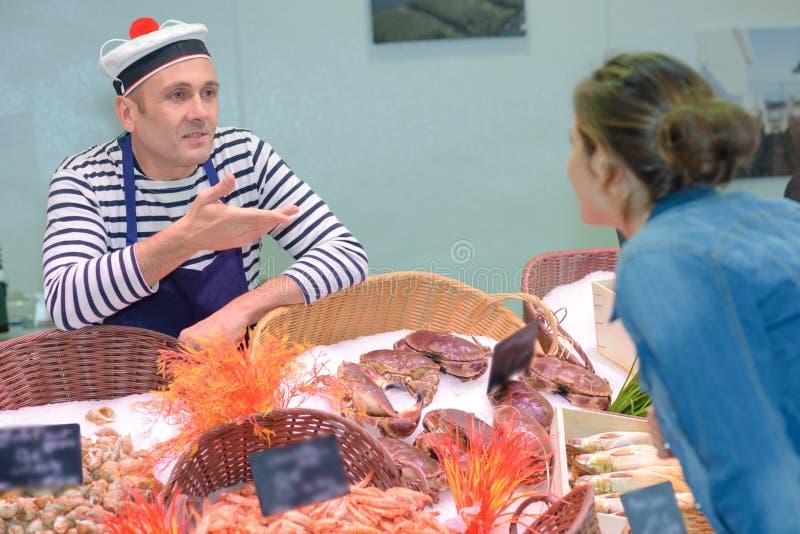 Il venditore sorridente maturo che aiuta il cliente femminile a scegliere ha raffreddato il pesce immagini stock libere da diritti