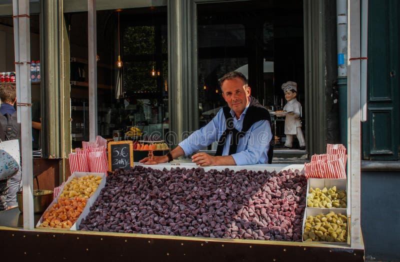 Il venditore vende il cuberdon a forma di cono fiammingo famoso delle caramelle sulla via di Gand fotografia stock