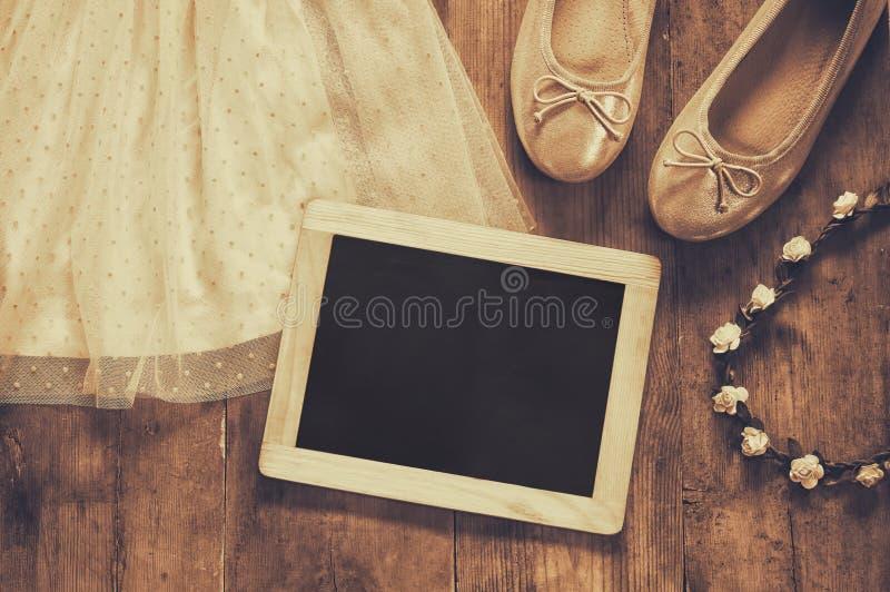 Il vestito chiffon d'annata della ragazza, diadema floreale accanto alle scarpe di balletto e lavagna in bianco fotografia stock